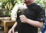 A child, boy standing with a butterfly on his hand. - MINF05019