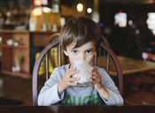 A boy, child drinking a glass of milk in a restaurant. - MINF05034