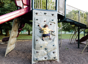 A child, boy climbing a climbing wall in a playground. - MINF05043