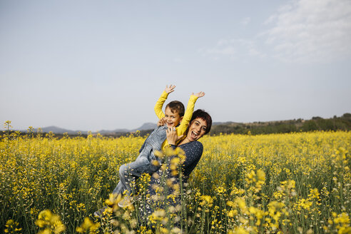Spain, portrait of happy mother and her little son up standing in rape field - JRFF01775