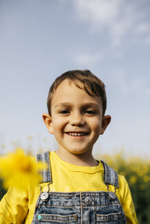 Portrait of happy little boy with picked yellow flower in nature - JRFF01781