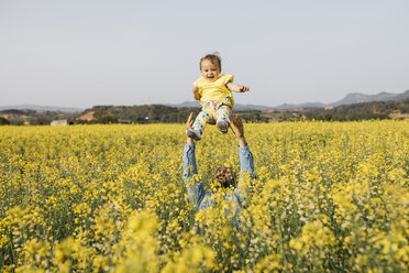 Spain, father and baby girl having fun  together in a rape field - JRFF01784