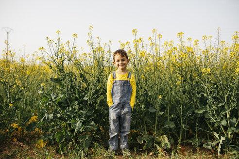 Portrait of smiling little boy standing in front of blooming rape field - JRFF01790
