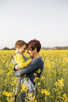 Mother standing with her little son in a rape field - JRFF01793