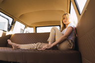 Portrait of young woman sitting in a van - KKAF01367