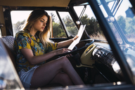 Young woman sitting in a van reading map - KKAF01370