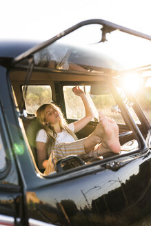 Young woman sitting in a van with feet up - KKAF01388