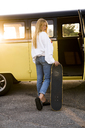 Young woman with skateboard standing outside at a vintage van - KKAF01391
