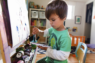 A four year boy sitting at an easel painting a picture. - MINF05082