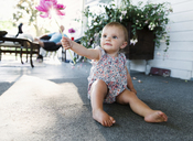 Baby girl sitting on house porch holding up a flower. - MINF05097