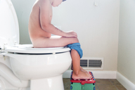 Boy, child sitting on the toilet in a family bathroom with his feet on a small blue step. - MINF05106