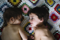 High angle view of young boy and girl lying on a crocheted blanket. - MINF05201