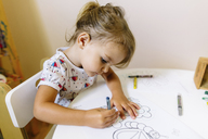 High angle view of young girl sitting at a table, drawing in colouring book. - MINF05225