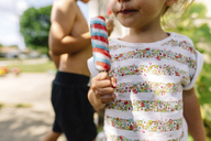 Close up of young girl standing outdoors, eating ice lolly. - MINF05231