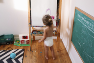 High angle rear view of young girl wearing nappy standing indoors at an easel, drawing, blackboard on wall. - MINF05237