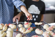 Close up of two children decorating biscuits with red sprinkles. - MINF05246