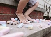 Drawing chalks on steps with a child's feet behind. - MINF05249