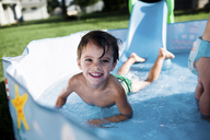 Boy, child, and baby girl playing in a paddling pool. - MINF05258