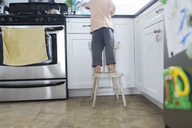 Boy, child, standing on a stool in a kitchen. - MINF05267