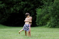 Young boy and girl in swimwear standing on a lawn, hugging. - MINF05312