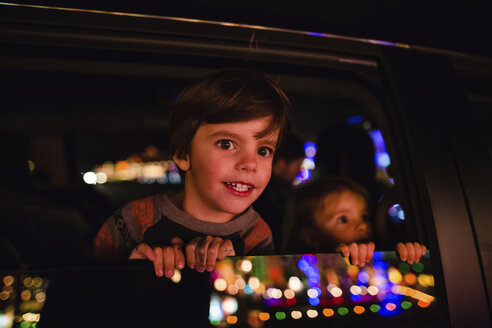Young boy and girl sitting in a car, looking out of window, reflection of illuminated Christmas decorations on the glass. - MINF05345