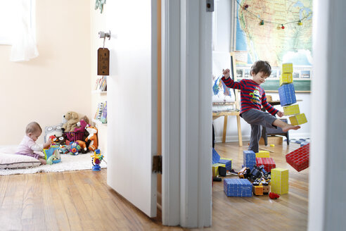 Two children in different rooms, a baby girl playing with toys and a boy kicking over a tower of building blocks. - MINF05354