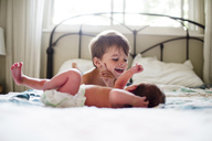 Young boy with brown hair and small baby lying on a bed. - MINF05381