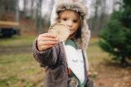 Young girl wearing furry hat standing outdoors, holding wooden disc towards camera. - MINF05387