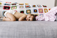Young girl wearing nappy lying on a sofa, looking at camera. - MINF05396