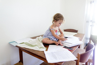 Young girl sitting on top of a wooden table covered in paperwork, holding pen, drawing. - MINF05411