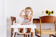 Young girl wearing dress sitting in a high chair, eating. - MINF05417