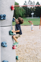Young boy with brown hair climbing up a climbing wall in a playground. - MINF05420