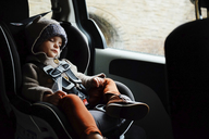 Young girl wearing coat and knit hat sitting in a child seat in the back of a car, sleeping. - MINF05438