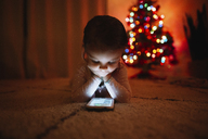 Young girl lying on her front on a carpet, looking at smart phone, illuminated Christmas Tree in the background. - MINF05441