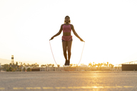Spain, Barcelona, young black woman skipping rope at sunrise - AFVF01275