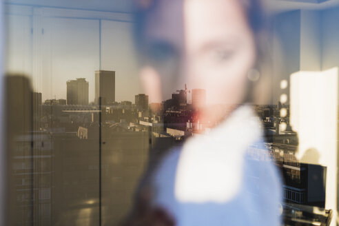 Spain, Madrid, blurred view of woman behind windowpane with reflection of the city - KKAF01419