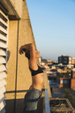 Young woman wearing bra standing on balcony - KKAF01428