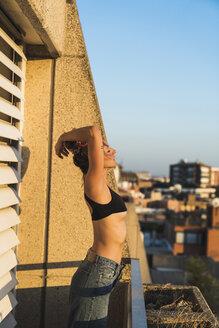 Young woman wearing bra standing on balcony - KKAF01428