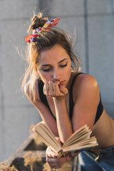 Young woman wearing bra reading book on balcony - KKAF01431