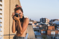 Happy topless young woman with camera taking pictures on balcony - KKAF01434