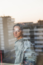 Portrait of young woman behind windowpane with reflection of the city - KKAF01443