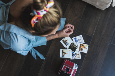 Young woman lying on the floor looking at instant photos of herself - KKAF01446