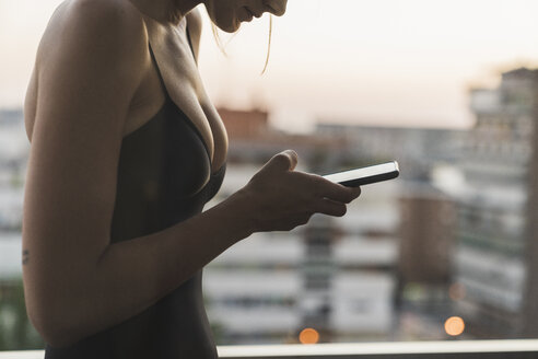 Close-up of young woman wearing black dress using cell phone on balcony - KKAF01452