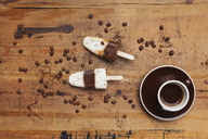 Homemade Espresso Macchiato ice lollies with cup of Espresso and coffee beans on wooden background - GWF05628