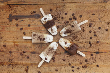 homemade Espresso Macchiato and Latte Macchiato ice lollies with coffee beans on wooden background - GWF05631