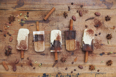 Homemade coffee and white chocolate ice lollies with winter spices on wooden background - GWF05634