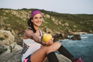 Sportive woman sitting on rocks, holding apple - RAEF02085