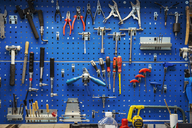 Large selection of hand tools organised and hung up neatly on a blue tool board on the wall of a factory or workspace. - MINF05531