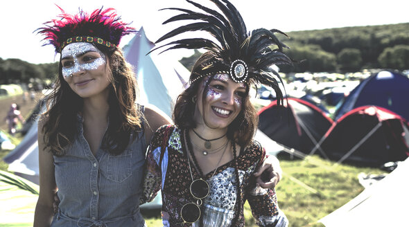 Two smiling young women at a summer music festival face painted, wearing feather headdress, standing among tents. - MINF05552