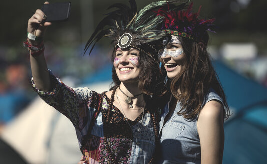 Two young women at a summer music festival faces painted, wearing feather headdress, taking selfie with smartphone. - MINF05555